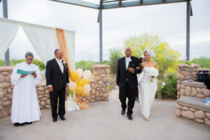 Father of the bride, the bride and the bride's dress attendant enter the ceremony space.  The officiant and the groom waiting at the altar.  Beautiful and slightly cloudy day at the Riparian Preserve