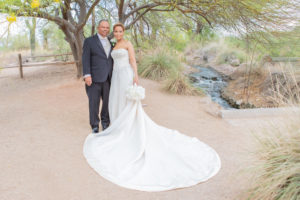 Bride and groom have a portrait picture taken.  They are at the Gilbert Riparian Preserve near a water feature, standing under a palo verde tree on a dirt path.