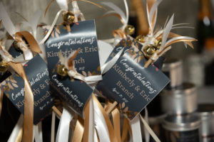 Congratulatory wands. gold, ivory and white ribbons, a jingle bell and a sign with the couples' name and wedding date.