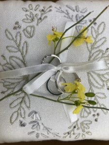 White ring bearer pillow with gold embroidery and beading.  The rings are tied on with the ivory ribbon.  placed on top of the rings and pillow are a couple of yellow blooms from a palo verde tree