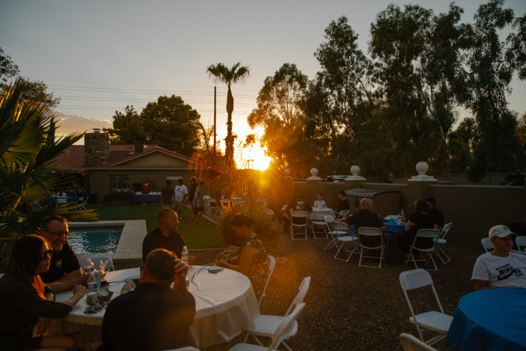 Large gathering of many different people in a backyard sitting in chairs at tables near a pool. How to have a Covid friendly event.