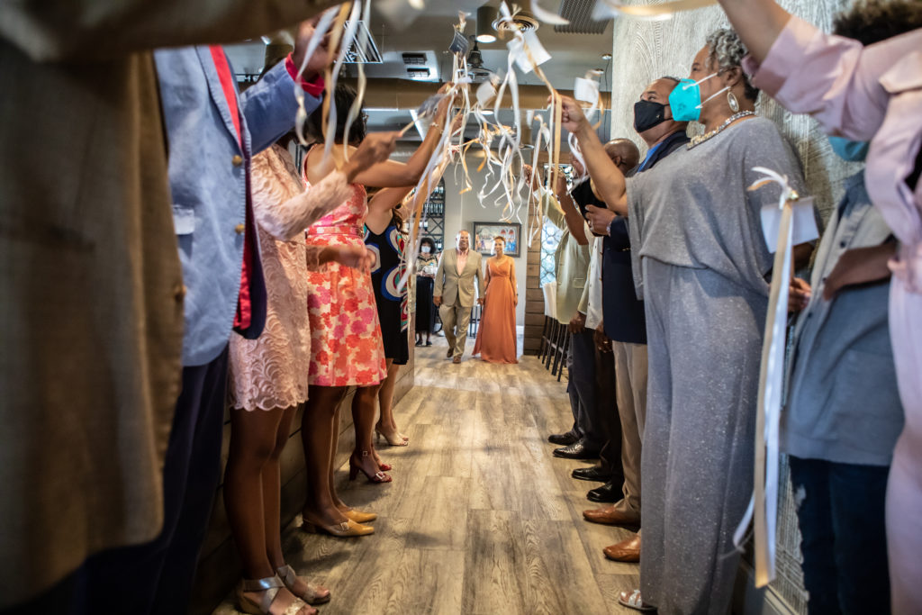 Intimate wedding dinner reception.  Guests are lined up on either side of the hallway with celebration wands. How to have a Covid friendly event.